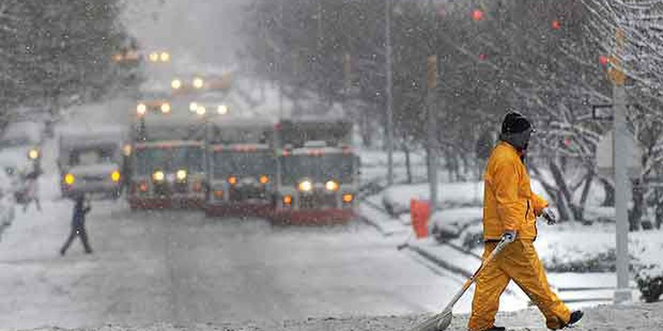 A man with a shovel crosses Park Avenue as snow plows line up behind him during a morning snowstorm February 10, 2010 on the east side of Manhattan in New York. The New York region is predicted to have 12-18 inches (30-45 cm) of snow by tonight.