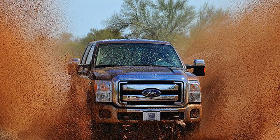 The 2011 Ford F-Series Super Duty splashes through water on an unimproved road. The 2011 Ford F-Series Super Duty has new available off-road features, including electronic locking rear differential, new Hill Descent Control and all-new transfer case skid plate.