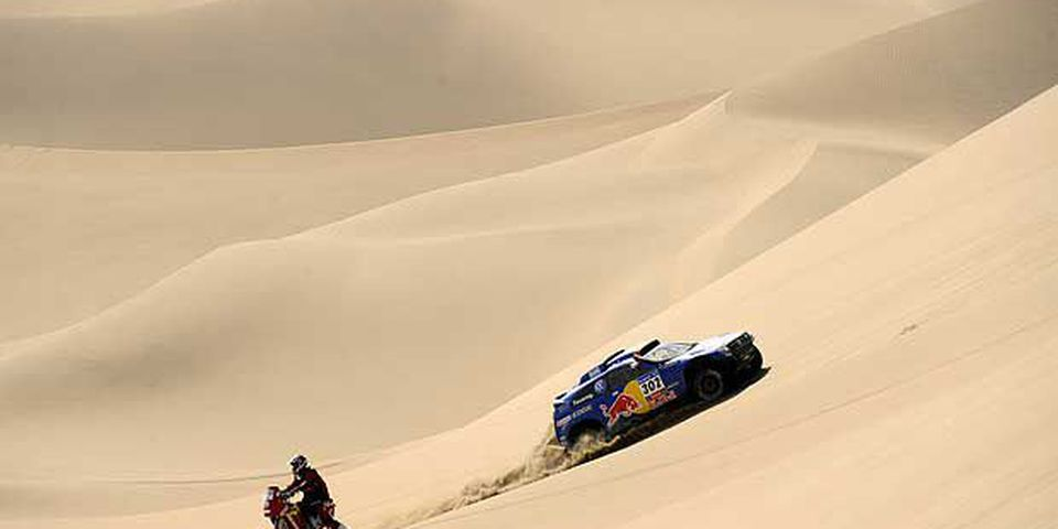 Qatar's driver Nasser Al-Attiyah steers his Volkswagen with German co-driver Timo Gottschalk as they pass China's biker Wenmin Su on his Jincheng on January 9, 2011 on the stage 7 Arica-Atacama of the 2011 Dakar Rally, in Chile.