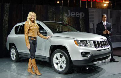 Chrysler Canada CEO Reid Bigland, right, introduces the 2011 Jeep Compass at the Montreal Auto show, noting that the woman does not come with the vehicle.