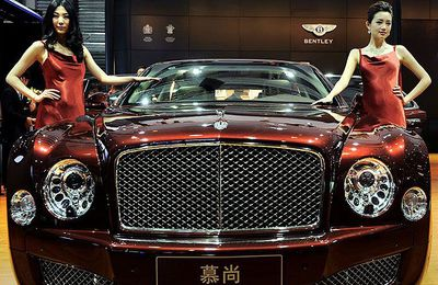Models pose by a Bentley displayed at the Shanghai Auto Show in Shanghai on April 20, 2011. About 2,000 car and parts makers from 20 countries are participating in the Shanghai auto show, showcasing 75 new car models, 19 of them making their world premieres.