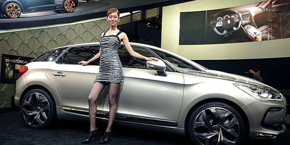 A model poses by the new Citroen DS5 at the Shanghai Auto Show in Shanghai on April 19, 2011. About 2,000 car and parts makers from 20 countries are participating in the Shanghai auto show, showcasing 75 new car models, 19 of them making world premieres.