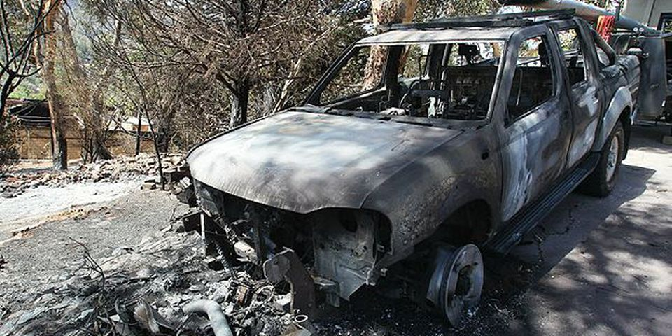 A car stands amongst bushfire devastation in the foothills suburb of Roleystone, a suburb of Perth on February 7, 2011. Wildfires destroyed at least 59 homes in Perth, Australia's fourth largest city, officials said, as soldiers fanned out for massive cleanup operations across the cyclone-hit northeast.