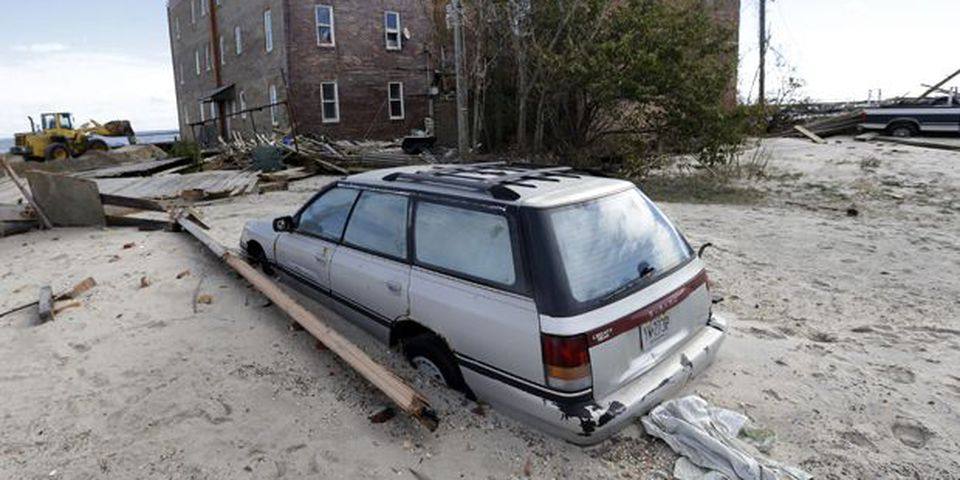 A car is partially buried by sand that was washed ashore by superstorm Sandy in Atlantic City, N.J.