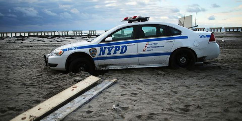 An abandoned police car is viewed on the heavily damaged beach in the Rockaway section of Brooklyn.