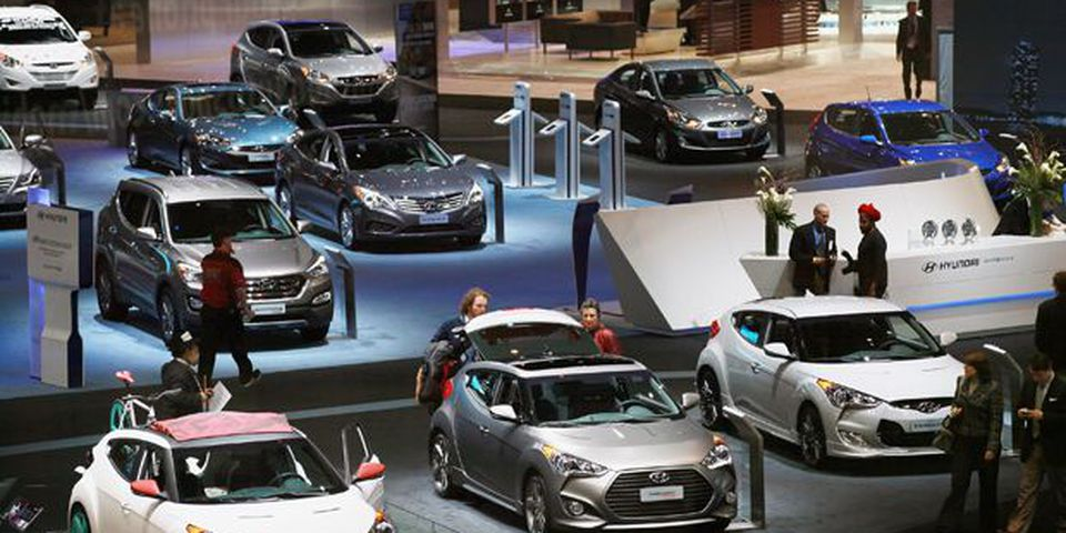 Visitors look over Hyundai cars during a media preview day at the Chicago Auto Show.