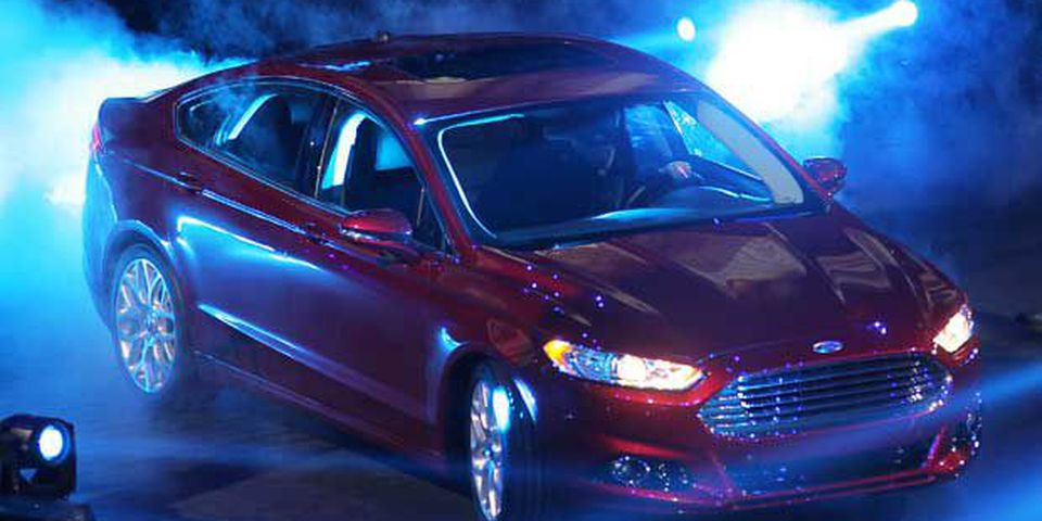 A 2013 Ford Fusion rolls onto the stage during the Ford presentation Monday, Jan. 9, 2012, at the Detroit International Auto Show in Detroit.