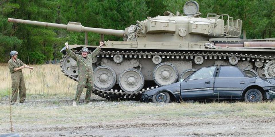 """Michael Noal from Vancouver (2nd L) celebrates after crushing a car with a 52-tonne ex-Australian army Centurion Tank called """"Maximus"""" at Tanks for Everything, a company where you can drive a tank over a car in Christchurch.   Tanks for Everything in Christchurch has a fleet of eight tanks, armoured personnel carriers and Jeeps, the largest of which can easily crush a family sedan pancake-flat in a crescendo of squealing metal and shattering glass."""