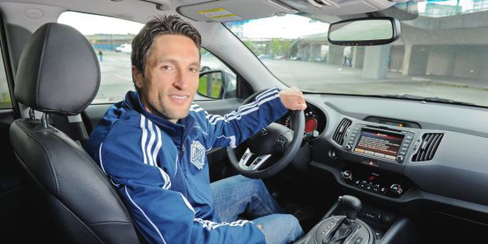 Vancouver Whitecaps player John Thorrington behind the wheel of a 2012 Kia Sportage outside BC Place. The crossover features a turbocharged 4-cylinder engine mated to a 6-speed manumatic transmission. This vehicle also features (below, left to right) a chunky sport steering wheel, attractive 18-inch alloy wheels and a two-panel panoramic sunroof.