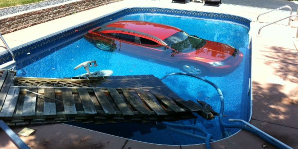 A car rest in a swimming pool after knocking down a fence in an Eat-end bank parking lot.