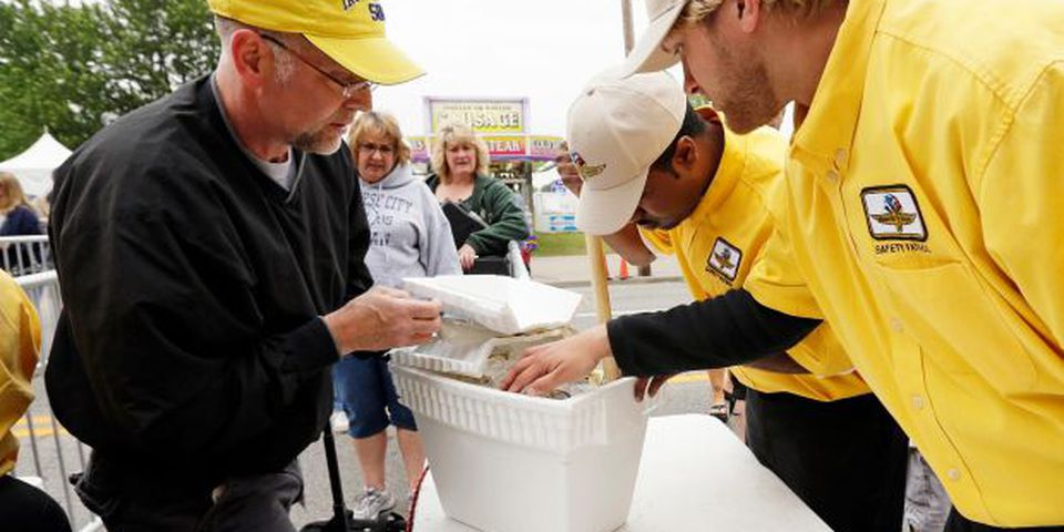 Indianapolis Motor Speedway Safety Patrol members inspect a patron's cooler as he enters the track for the Indianapolis 500.