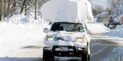 A vehicle, with a large chunk of snow on its top drives along Route 20 after digging out after a massive snow fall in Lancaster, N.Y. Wednesday, Nov. 19, 2014. Another two to three feet of snow is expected in the area.