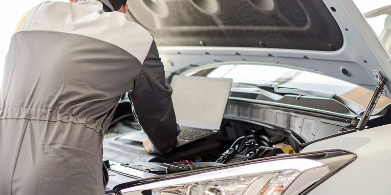 Mechanic with laptop diagnoses car in workshop.