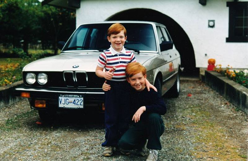 Brendan McAleer, kneeling, poses with younger brother Kieran in front of their father's BMW 535i.