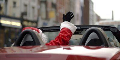 Santa waiving from his red deliviery car
