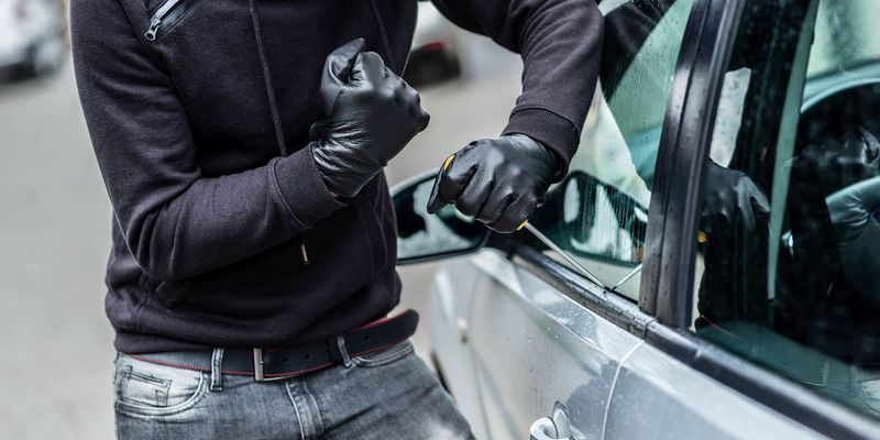 A man dressed in black with a balaclava on his head trying to break into a car.