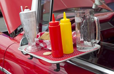 A drive-in restaurant's condiment tray hanging off the window of a classic Chevy convertible