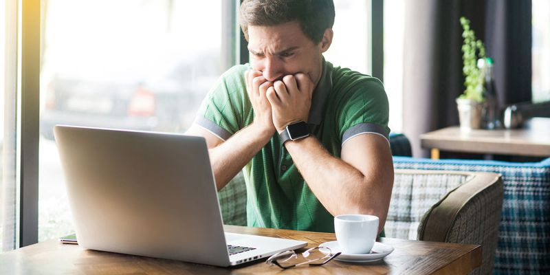 Young nervous businessman in green t-shirt sitting and working on laptop, bitting his nails and looking at screen with worry face. business and freelancing concept.