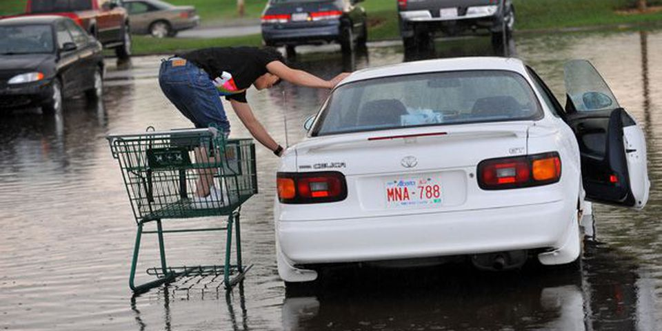 Isaac Yu uses a shopping cart to get to his car parked in the deep rain water after a rain storm in Edmonton in this file photo.