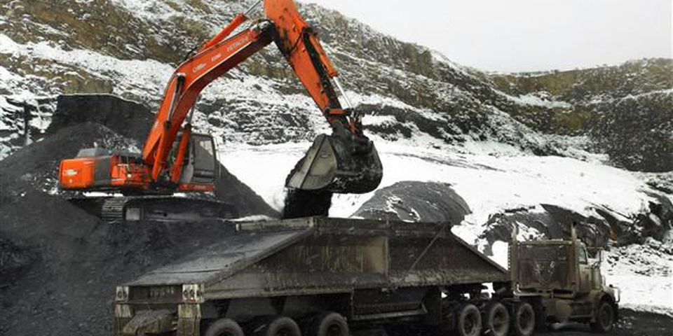 A power shovel loads a 25 tonne coal hauling truck at Grande Cache Coal's open pit mine above the tree line, 2020 metres above sea level.