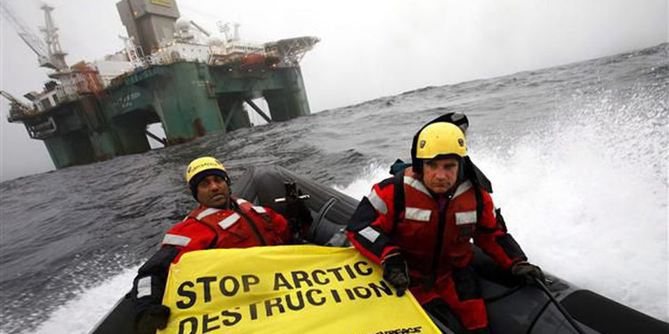 "Greenpeace members hold a banner aboard a boat near an oil rig in the Davis Strait, off Greenland's west coast in this photo provided by Greenpeace International. There is a ""growing radicalized environmentalist faction"" in Canada that is opposed to the country's energy sector policies, warns a newly declassified intelligence report."