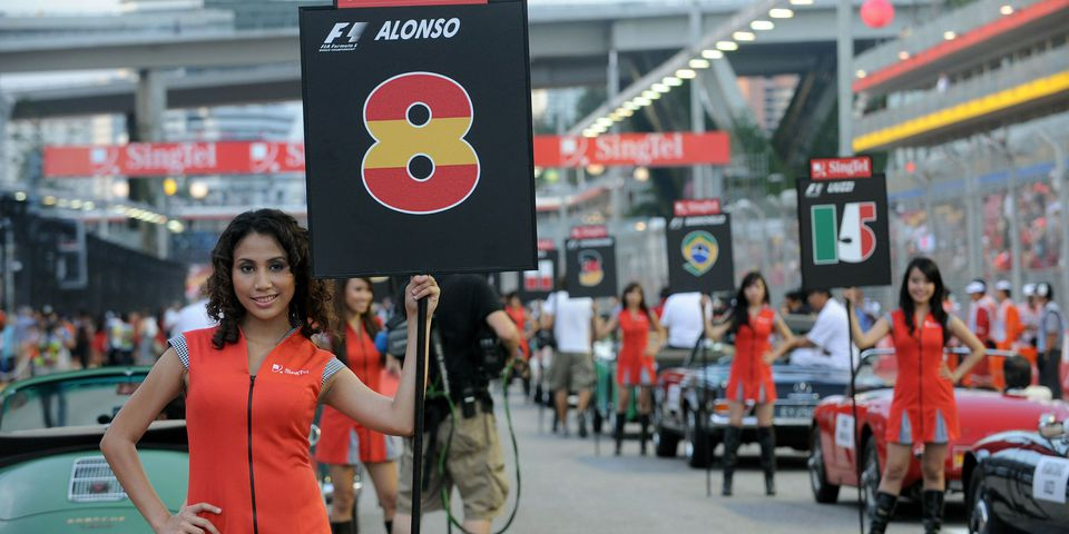 Grid girls stand next to vintage cars