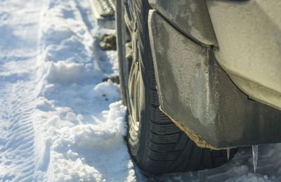 A rear of a vehicle with icicles on the splash guard