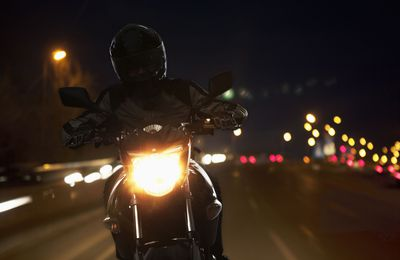 Young Man riding a motorcycle at night