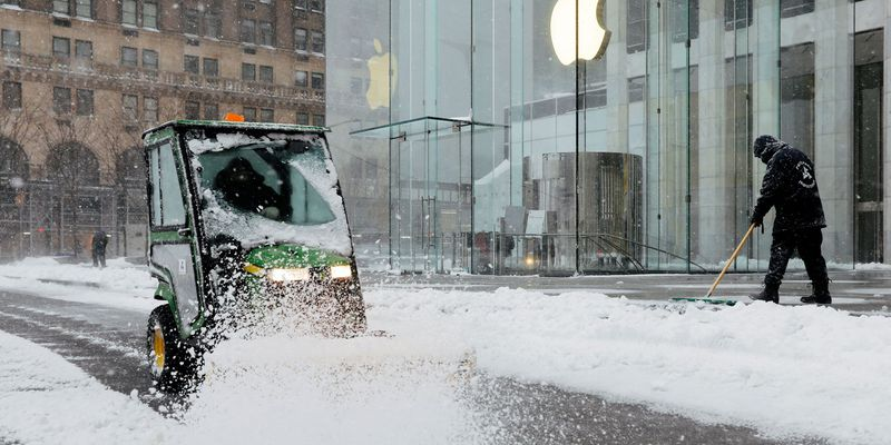 Workers clear a street outside the Apple Fifth Avenue during a snow storm in New York