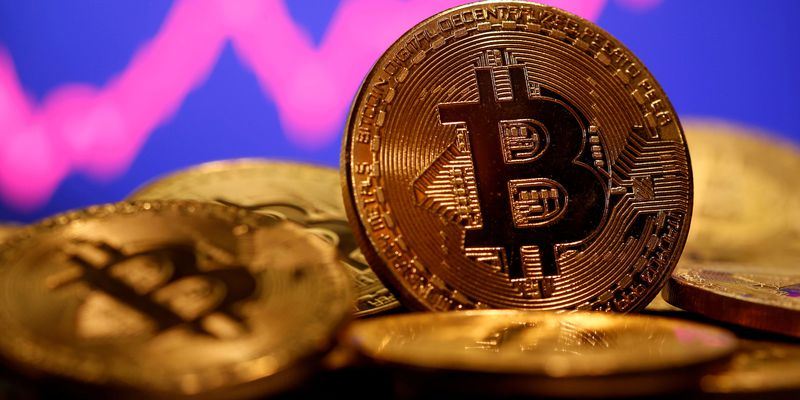 FILE PHOTO: FILE PHOTO: FILE PHOTO: A representation of virtual currency Bitcoin is seen in front of a stock graph in this illustration taken