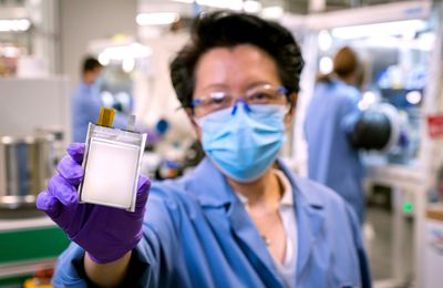 A GM employee poses with an example of the company's next-generation lithium metal batteries