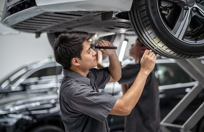 mechanic Checking and torch tire in maintainance service center which is a part of showroom, technician or engineer professional work for customer, car repair concept