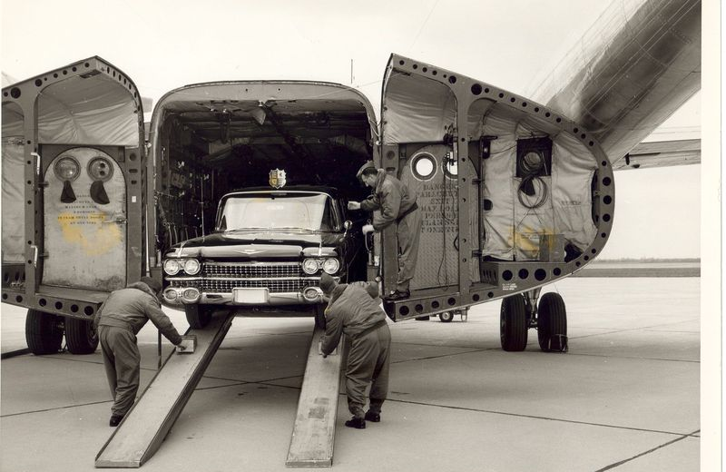 "1959 75 Series Cadillac Fleetwood limousine being unloaded from the RCAF C-119 ""Flying Boxcar"" used to move it around Canada for Queen Elizabeth II and Prince Philip's Royal Tour"