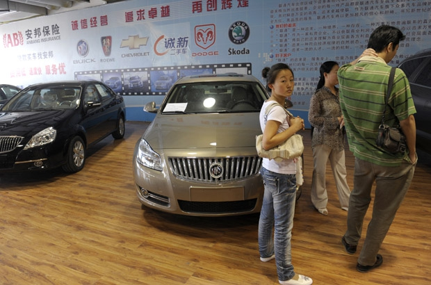 A woman stands by new Buick cars made by Shanghai General Motors at a car market in Beijing on September 9, 2009. China's auto sales soared 81.7 percent in August from a year earlier to 1.14 million units, breaking the one million unit mark for a sixth consecutive month, an industry association said.
