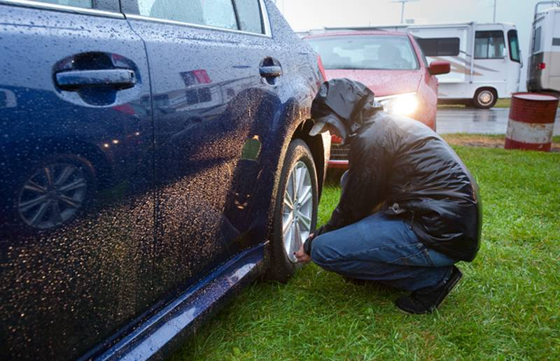 A technician checks tire pressures on a Subaru Legacy in the morning rain before comparative evaluations resume at TestFest