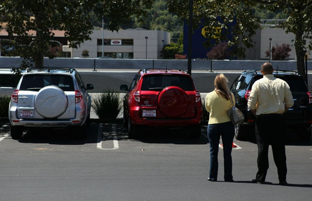 A woman looks at new Toyotas with a salesman in this file photo.
