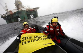 """Greenpeace members hold a banner aboard a boat near an oil rig in the Davis Strait, off Greenland's west coast in this photo provided by Greenpeace International. There is a """"growing radicalized environmentalist faction"""" in Canada that is opposed to the country's energy sector policies, warns a newly declassified intelligence report."""
