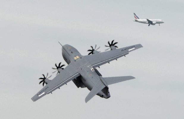 Pilots of an Airbus A400M present their flying display during a preparation at Le Bourget on June 16, 2013 as an Air France plane crosses the sky far in the background on the eve of the opening of the International Paris Air show.