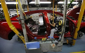 A Mazda employee works on the assembly line of the Mazda6 (Atenza) model at its plant in Hofu, Yamaguchi prefecture, southwestern Japan, Tuesday, Aug. 27, 2013. Mazda, the longtime also-ran of Japanese automakers, shows a new super-efficient plant that's rolling off vehicles at a stunning rate of one every 54 seconds. The plant is part of the reason why Mazda Motor Corp. has managed to defy skeptics who've predicted fates ranging from bankruptcy to a buyout by Chinese interests. (AP Photo/Shizuo