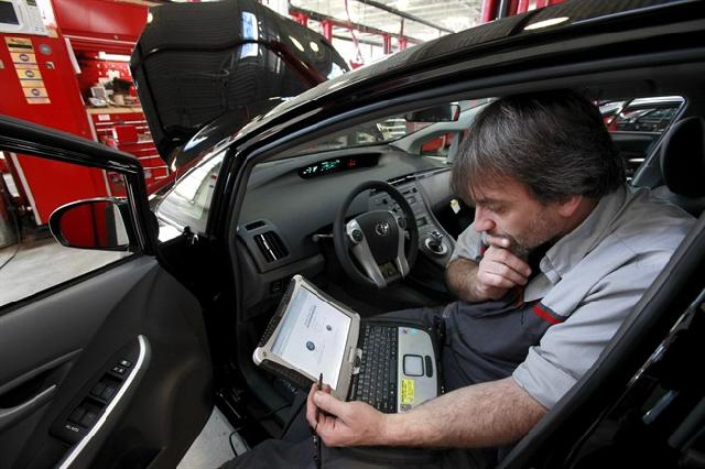 FILE - In this Feb. 9, 2010 file photo, master diagnostic technician Kurt Juergens, of Foxborough, Mass., uses a laptop computer to diagnose and repair the brake system on a 2010 Toyota Prius in the repair shop of a Toyota dealership, in Norwood, Mass. A pair of hackers maneuvered their way into the computer systems of a 2010 Toyota Prius and 2010 Ford Escape through a port used by mechanics. The hackers showed that they could slam on the brakes at freeway speeds, jerk the steering wheel or even