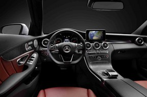 The interior of the 2015 C-Class features swoopy, black lines and a prominent central display.