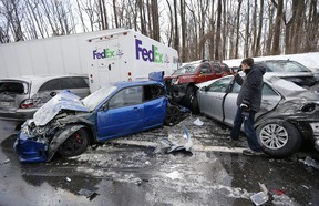 A man inspects vehicles piled up in an accident recently in Bensalem, PA.