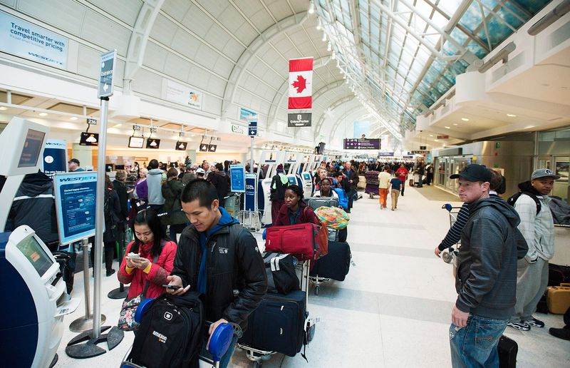 Passengers line up during flight delays and cancellations due to extreme cold weather at Pearson International Airport in Toronto on Tuesday, Jan. 7, 2014.