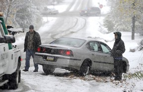 Drivers wait for a tow truck to pull their car from a ditch.
