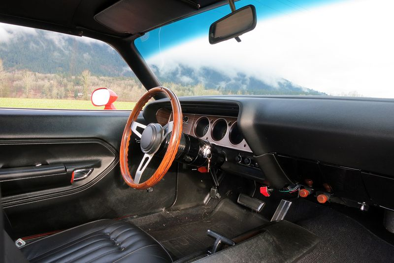 The 'Cuda's cockpit is spacious, but the thin-rimmed wooden steering wheel requires plenty of muscle to manipulate at slower speeds.