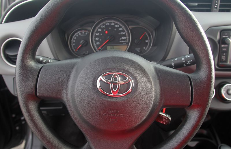 The steering wheel of the 2015 Toyota Yaris LE.