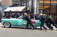 Columnist Alyn Edwards, centre, Red Robinson, Rich Elwood and spectators push Natalie Speckmaier's 1955 Ford Thunderbird to the finish line during Vancouver's recent St. Patrick's Day Parade.