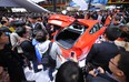 Visitors look at an Audi S7 on the opening day of the Shanghai auto show on April 21, 2013.