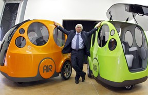 """Guy Negre, head of MDI (Motor development International) company, stands between """"Airpod One"""" prototypes of non-polluting minicars driven with a joystick, activated by compressed air in this October 9, 2008 file photo in Nice, southern France."""