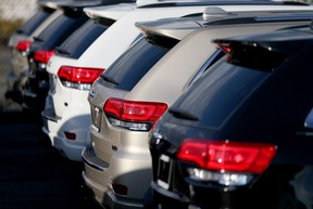 A row of Jeep Grand Cherokee SUVs on a dealer lot